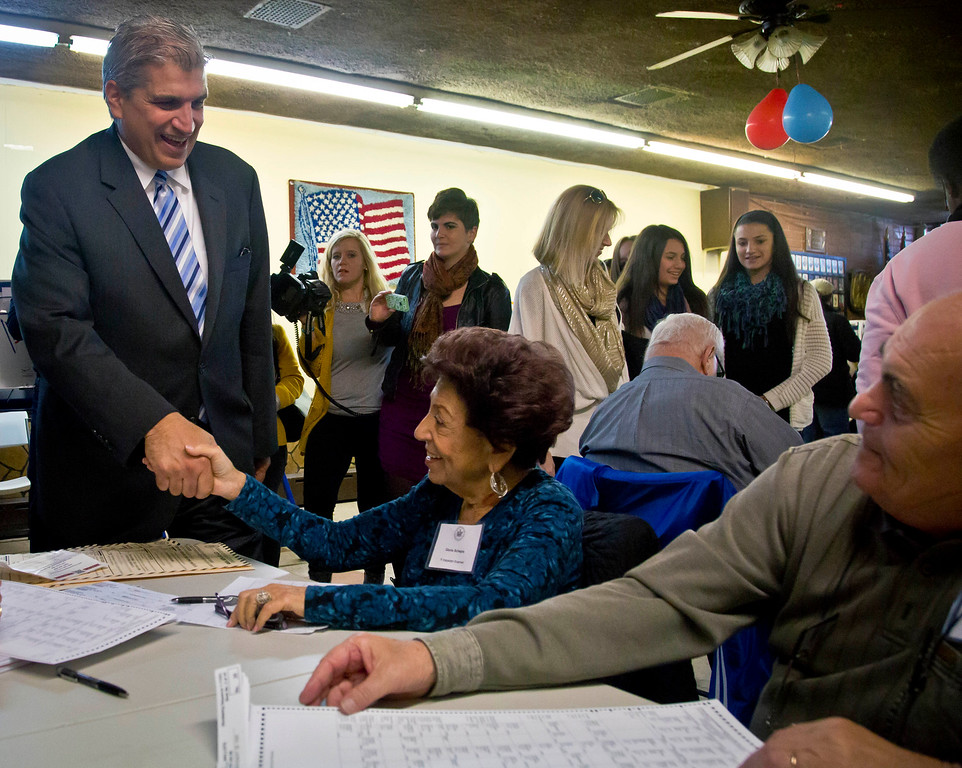 . Democratic U.S. House candidate, former Democratic City Councilman Domenic Recchia, left, shake hands with polling station workers as he arrives to cast his vote, Tuesday Nov. 4, 2014 in New York. Recchia is challenging embattled two-term Republican Staten Island U.S. Rep. Michael Grimm. (AP Photo/Bebeto Matthews)