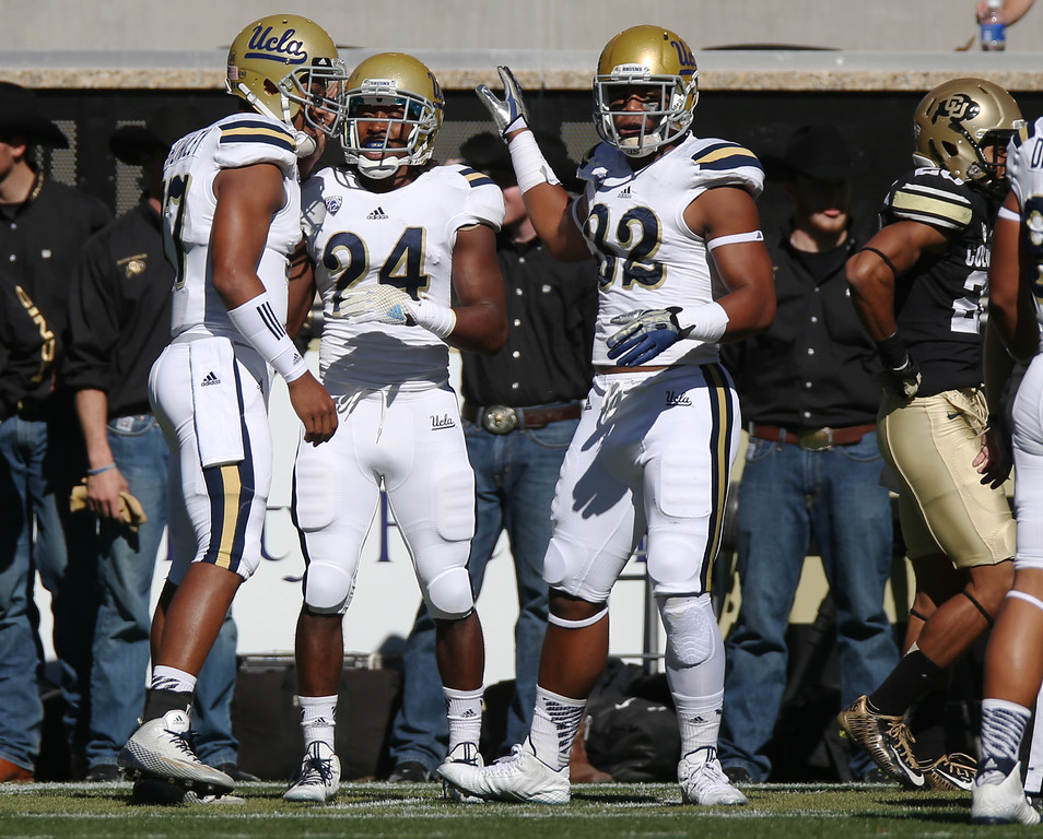 . From left, UCLA quarterback Brett Hundley celebrates with running back Paul Perkins and fullback Nate Iese after Perkins\' 93-yard touchdown run as Colorado defensive back Greg Henderson walks away in the first quarter of an NCAA football game in Boulder, Colo., on Saturday, Oct. 25, 2014. (AP Photo/David Zalubowski)