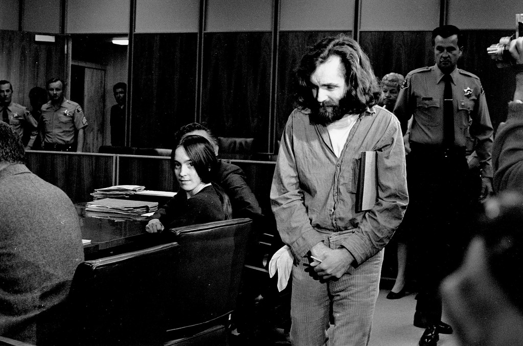 . Charles Manson walks into the courtroom in Santa Monica, Ca. on Oct. 13, 1970. Manson and Susan Atkins, seated, a member of his family of followers, are to plead on charges of murdering a Malibu musician, Gary Hinman. When his name was called, Manson stood, folded his arms, and turned his back on the judge. Atkins did the same. The court then entered pleas of innocent. Both are on trial in Los Angeles for killings that included actress Sharon Tate. (AP Photo)
