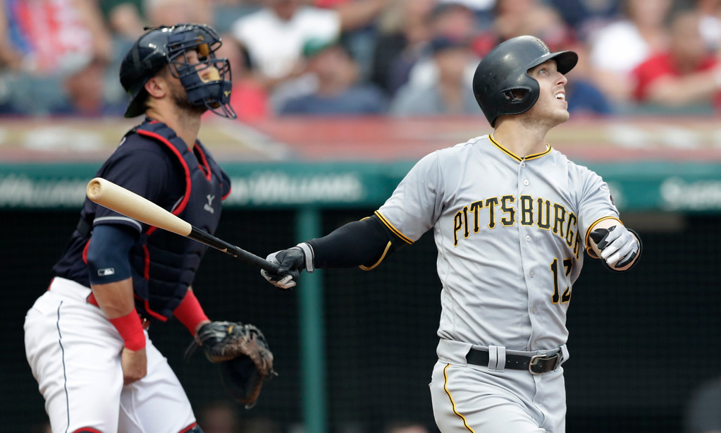 . Pittsburgh Pirates\' Corey Dickerson watches his ball after hitting a two-run triple off Cleveland Indians starting pitcher Shane Bieber in the second inning of a baseball game, Tuesday, July 24, 2018, in Cleveland. Indians catcher Yan Gomes watches. (AP Photo/Tony Dejak)