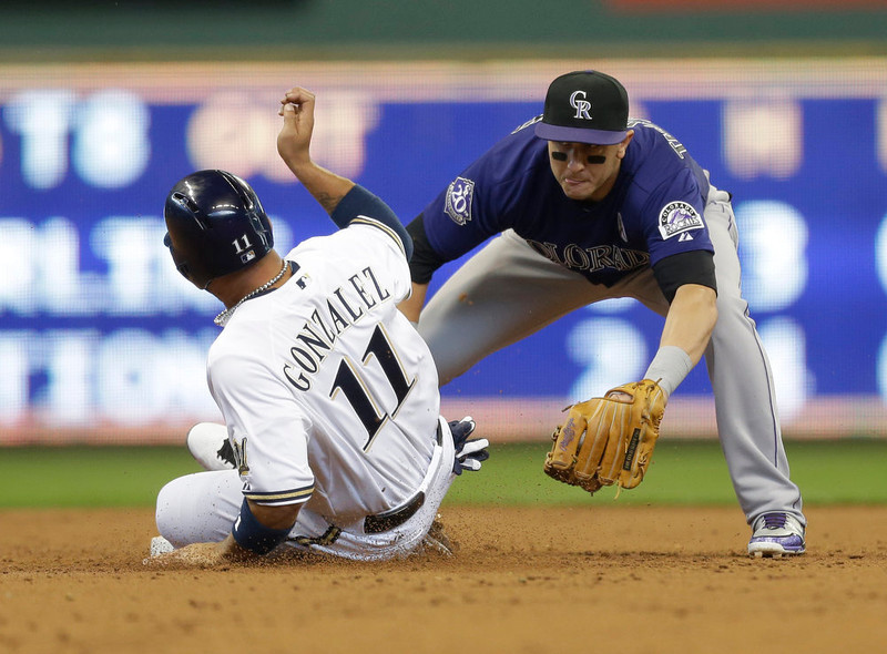 . Colorado Rockies\' Troy Tulowitzki, right, tags out Milwaukee Brewers\' Alex Gonzalez in the second inning of an Opening Day baseball game  Monday, April 1, 2013, in Milwaukee. (AP Photo/Jeffrey Phelps)