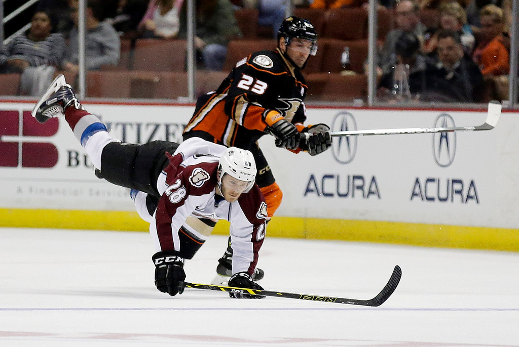 . Anaheim Ducks defenseman Francois Beauchemin, right, knocks Colorado Avalanche center Paul Carey to the ice during the first period of an NHL hockey preseason game in Anaheim, Calif., Monday, Sept. 22, 2014. (AP Photo/Chris Carlson)
