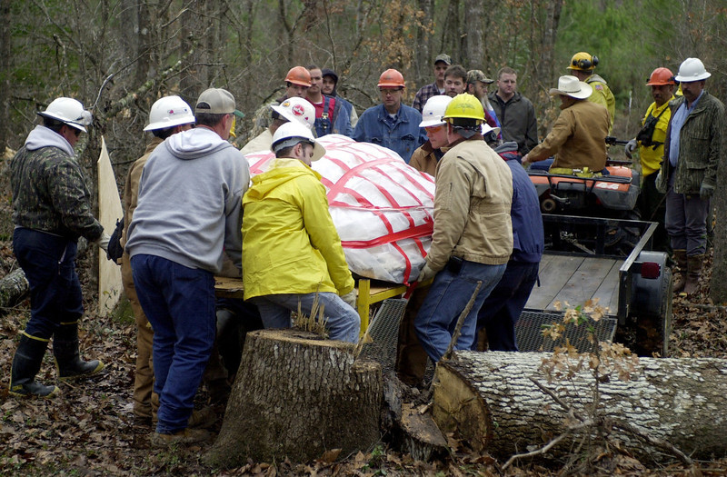. Workers remove a piece of space shuttle Columbia\'s nose cone  near Hemphill, Texas, Wednesday, Feb. 5, 2003. The discovery on Monday of one of the biggest and most recognizable pieces of Columbia, the nose cone, underscored how hard it will be to find the thousands of much-smaller bits of debris. The shuttle part, about 4 feet across, was discovered drilled into the ground in a deep thicket near Hemphill by two men who were scouring their land for debris. (AP Photo/Eric Gay)