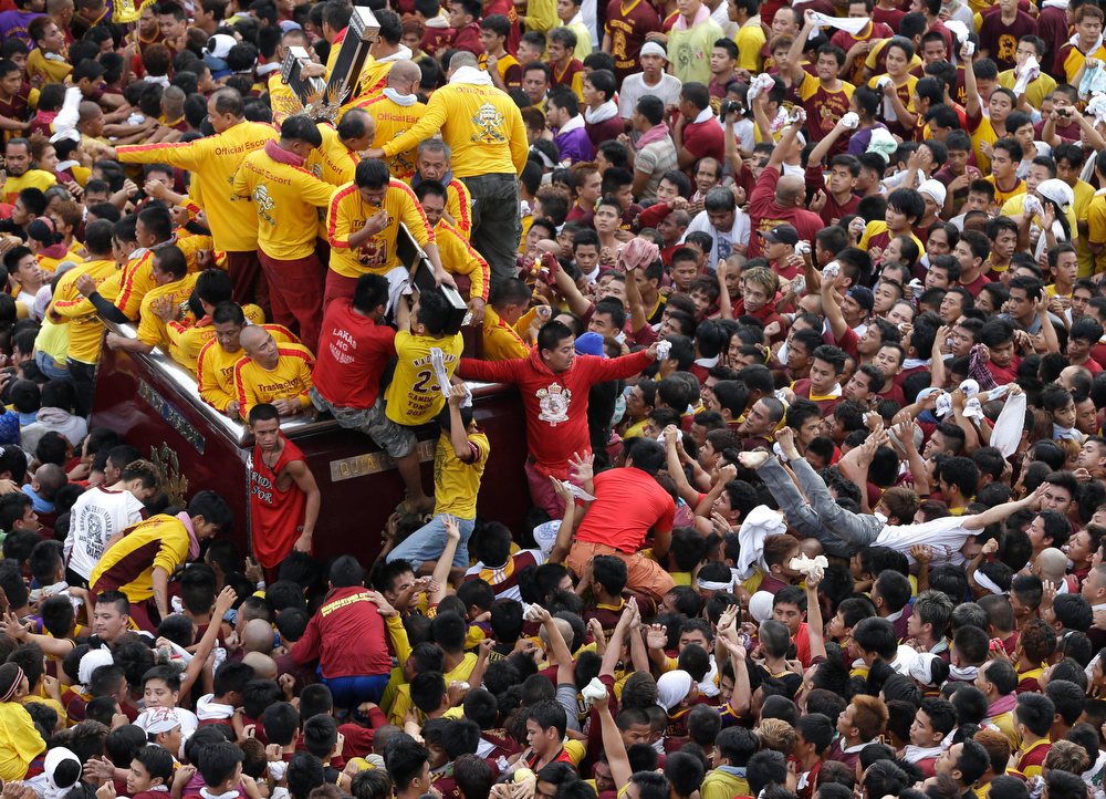 . A Catholic devotee dives back to the crowd after managing to kiss the rear end of the cross of the centuries-old image of the Black Nazarene in a raucous celebration on its feast day Wednesday Jan. 9, 2013 in Manila, Philippines. The annual procession by hundreds of thousands of devotees is now becoming to be a tourist attraction.  More than a hundred devotees were treated for mostly minor injuries. (AP Photo/Bullit Marquez)