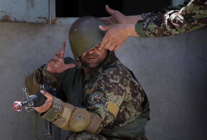 . A military instructor adjusts the helmet of an Afghan Army soldier during a house-to-house search at a training facility in the outskirts of Kabul, Afghanistan on Wednesday, May 8, 2013. In roughly 90 percent of the country, Afghan police and soldiers are taking the fight to the Taliban alone, a first in 12 years of war. U.S. and NATO soldiers have slipped quietly into the background, taking on the role of advisor and providing backup when needed.  (AP Photo/Anja Niedringhaus)