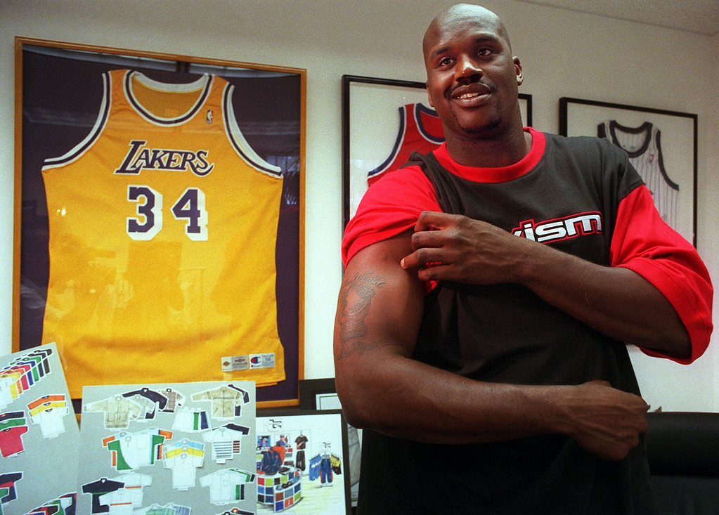 """. Los Angeles Lakers\' center Shaquille O\'Neal reveals his tattoo which includes the acronym TWISM, meaning \""""The World is Mine,\"""" a fist holding a globe, during the public unveiling of his company TWISM, Inc., in Compton, Calif., Thursday, Nov. 6, 1997.  TWISM, Inc., an apparel-printing facility currently producing up to 11,000 sportswear apparel units per day, represents the belief by O\'Neal, that it is possible for all people to achieve their goals. (AP Photo/Damian Dovarganes)"""