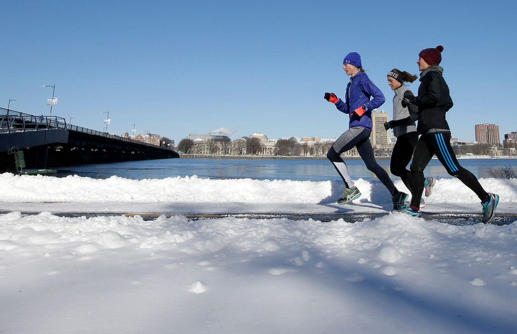 . Runners make their way along a path next to the Charles River, Sunday, Jan. 8, 2017, in Boston. A storm that wreaked havoc along the East Coast arrived in southern New England Saturday, making travel treacherous throughout the region. (AP Photo/Steven Senne)