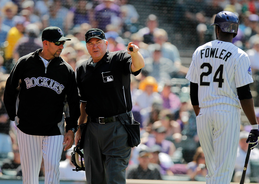 . Colorado Rockies manager Walt Weiss, left, talks to home plate umpire Dana DeMuth about a replay of Dexter Fowler\'s (24) hit to right field that was called foul during the inning of a baseball game Wednesday, May 22, 2013 in Denver. The Rockies won 4-1.(AP Photo/Barry Gutierrez)