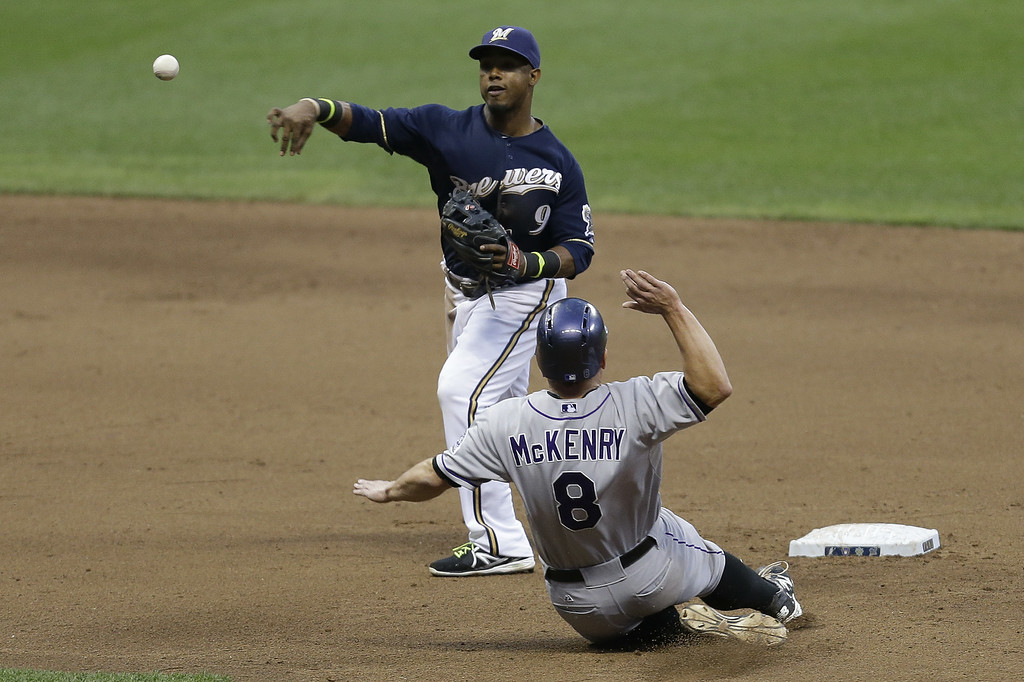 . MILWAUKEE, WI - JUNE 27: Jean Segura #9 of the Milwaukee Brewers turns the double play as Michael McKenry #8 of the Colorado Rockies slides into second base in the top of the fifth inning at Miller Park on June 27, 2014 in Milwaukee, Wisconsin. (Photo by Mike McGinnis/Getty Images)
