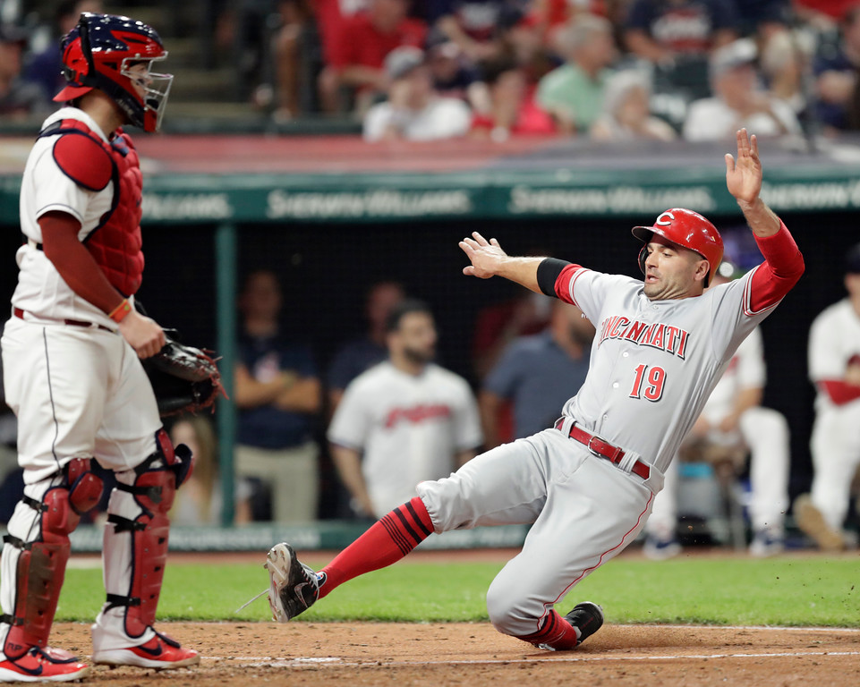 . Cincinnati Reds\' Joey Votto, right, scores as Cleveland Indians catcher Roberto Perez watches during the ninth inning of a baseball game Tuesday, July 10, 2018, in Cleveland. The Reds won 7-4. (AP Photo/Tony Dejak)