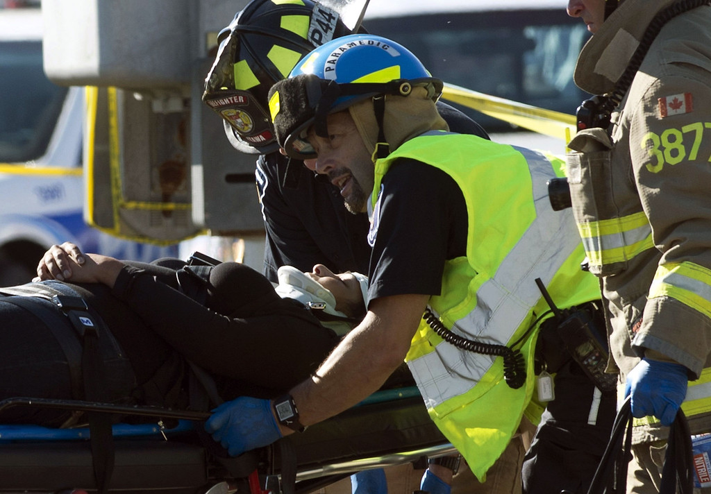 . Firefighters and paramedics transport a passenger to a waiting ambulance after a Via Rail train and city bus collide, Wednesday Sept. 18, 2013 in Ottawa, Canada. Witnesses said the bus went through a closed crossing barrier. (AP Photo/The Canadian Press, Adrian Wyld)