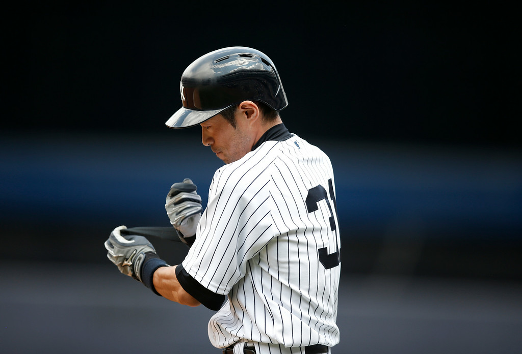 . New York Yankees right fielder Ichiro Suzuki removes his batting gear after his third-inning base hit in a baseball game against the Detroit Tigers at Yankee Stadium in New York, Thursday, Aug. 7, 2014.  (AP Photo/Kathy Willens)