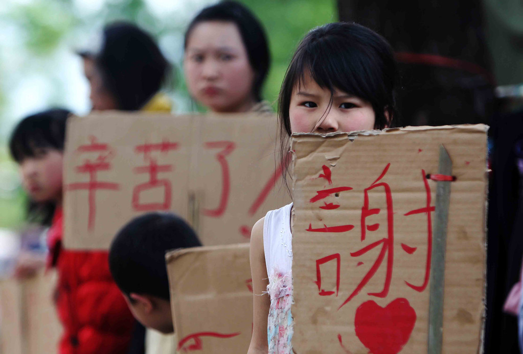 . LUSHAN, CHINA - APRIL 24:  (CHINA OUT) Local children carrying cardboard placards reading \'Thank you\' stand by the roadside on April 24, 2013 in Lushan County, China. A powerful earthquake struck the steep hills of China\'s southwestern Sichuan province on the morning of April 20, leaving at least 196 people dead and more than 12,200 injured.  (Photo by ChinaFotoPress/ChinaFotoPress via Getty Images)