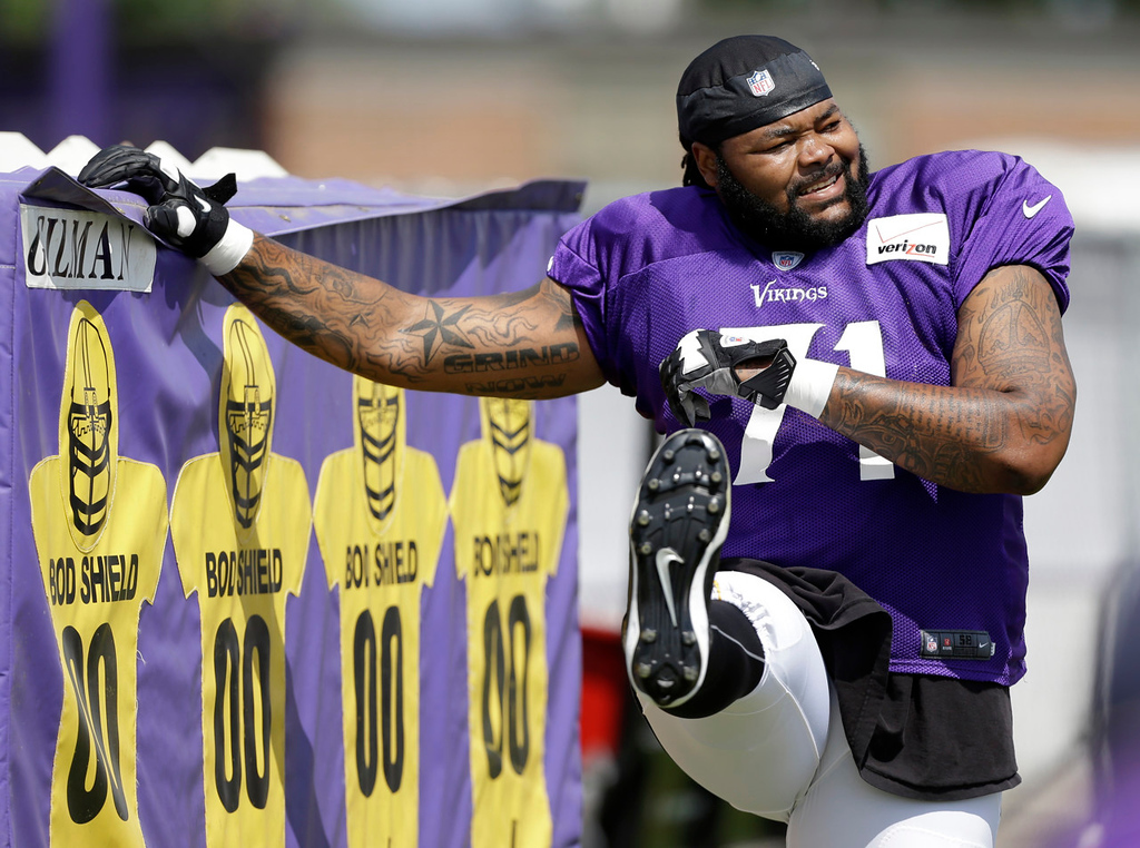 . Vikings offensive tackle Phil Loadholt stretches before drills begin. (AP Photo/Charlie Neibergall)