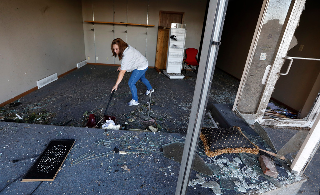 . Stephanie Moz, of Marshalltown, Iowa, cleans out her tornado-damaged business on Main Street, Thursday, July 19, 2018, in Marshalltown, Iowa. Several buildings were damaged by a tornado in the main business district in town including the historic courthouse. (AP Photo/Charlie Neibergall)