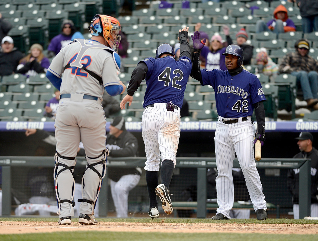 . Michael Cuddyer of the Colorado Rockies high fives Chris Nelson after scoring on a Wilin Rosario single in the second inning April 16, 2013 at Coors Field. (Photo By John Leyba/The Denver Post)