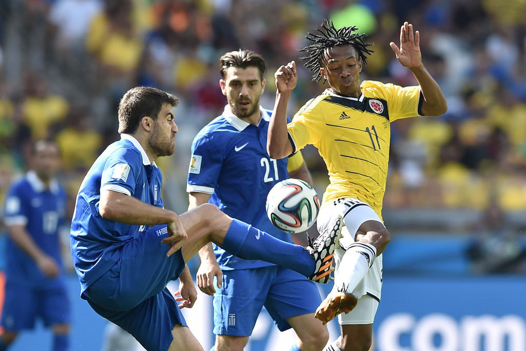 . Colombia\'s midfielder Juan Cuadrado (R) in action during a group C football match between Colombia and Greece at the Mineirao Arena in Belo Horizonte during the 2014 FIFA World Cup on June 14, 2014.    AFP PHOTO / ARIS MESSINIS