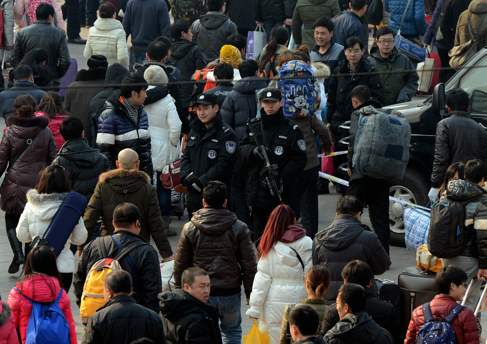 Description of . Armed Chinese police (C) stand guard as the annual Lunar New Year exodus begins at Beijing train station on January 26, 2013.  The holiday also known as the Spring Festival sees tens of millions of migrant workers who provide the labour in the country\'s prosperous cities return to their villages and towns to spend time with the families left behind.    MARK RALSTON/AFP/Getty Images