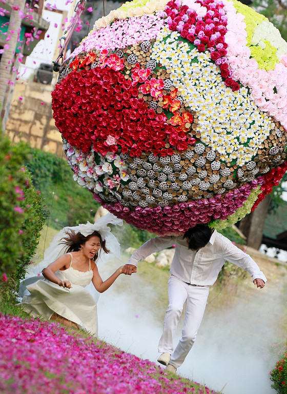 . Chutuma Tapoatong, left, and Sopon Tapoatong try to run away from a giant flower ball as a part of an adventure-themed wedding ceremony in Prachinburi province, Thailand, Wednesday, Feb. 13, 2013, on the eve of Valentine\'s Day. Three couples participated in the ceremony. (AP Photo/Wason Wanichakorn)