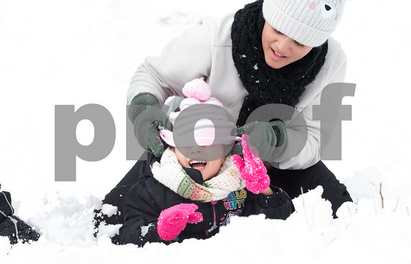 03/08/18 Wesley Bunnell | Staff Dayleen Eatmon helps sister Daynalis Eatmon , age 3, with her hat as they make their was back up a hill next to Smith Elementary School on Thursday after a sledding run. A winter storm dumped heavy snow throughout the area Wednesday afternoon into the evening.