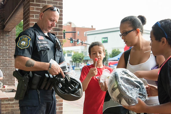 08/07/18 Wesley Bunnell | Staff New Britain Police held their annual National Night Out 2018 on Tuesday evening in a blocked off Central Park area. Officer Joe Milhomens helps Cesar Borrero, age 8 2nd left, mom Lizmary Reyes and Juelz Vega, age 11, pick out the right size bicycle helmets.