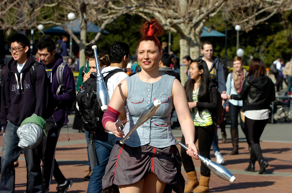 """. Circus Oz performer Hazel Bock juggles clubs as the Australian circus group performs on Sproul Plaza at the University of California to preview their new show \""""From the Ground Up\"""" in Berkeley, Calif. on Wednesday, Feb. 13, 2013. (Kristopher Skinner/Staff)"""