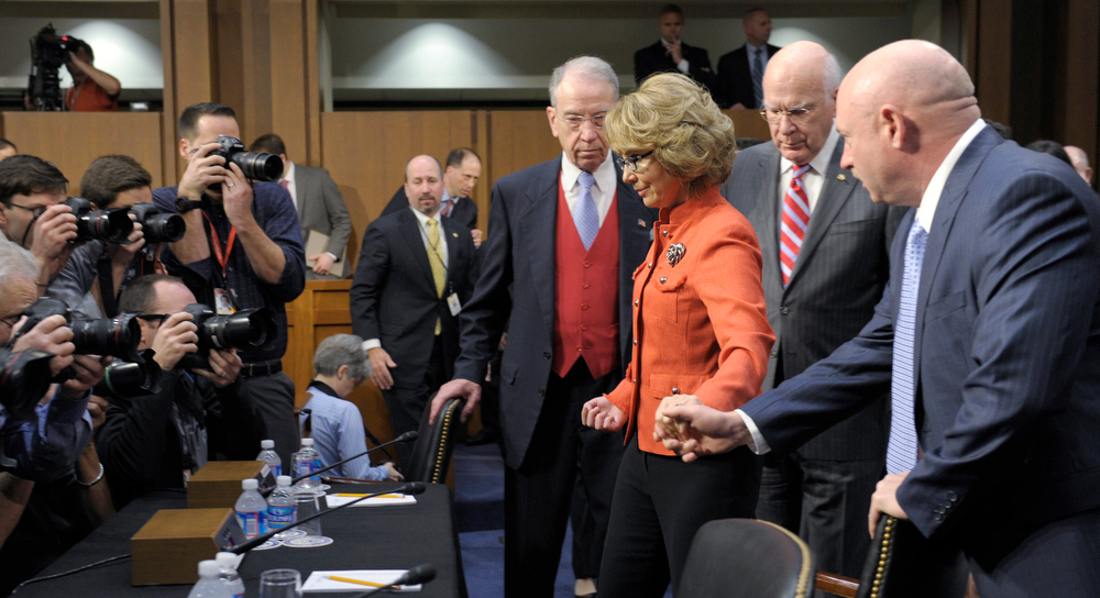 Description of . Former Arizona Rep. Gabrielle Giffords, center, who was seriously injured in the mass shooting that killed six people in Tucson, Ariz. two years ago, arrives with her husband Mark Kelly, right, on Capitol Hill in Washington, Wednesday, Jan. 30, 2013,  to give an opening statement before the Senate Judiciary Committee hearing on gun violence. Walking with Giffords is Senate Judiciary Committee Chairman Sen. Patrick Leahy, D-Vt., second from right, and the Committee's Ranking Republican, Sen. Chuck Grassley, R-Iowa. (AP Photo/Susan Walsh)