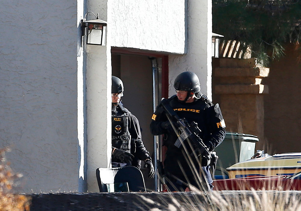 . Members of the Phoenix Police Department SWAT team exit the garage at the home of a suspected gunman who opened fire at a Phoenix office building, wounding three people, one of them critically, and setting off a manhunt that led police to surround his house for several hours before they discovered he wasn\'t there, Wednesday, Jan. 30, 2013, in Phoenix.  Authorities believe there was only one shooter, but have not identified him or a possible motive for the shooting. They don\'t believe the midmorning shooting at the complex was a random act. (AP Photo/Ross D. Franklin)