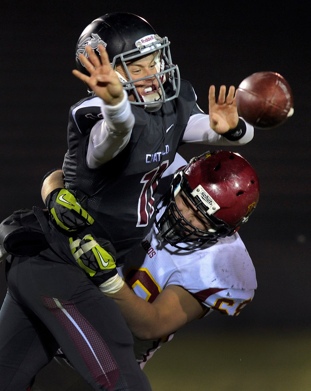 . Chatfield quarterback Kyle Winkler (11) tried to get rid of the ball as he was dragged down by Lobos linebacker Ryan Murphy (68) in the second half.  Photo By Karl Gehring/The Denver Post