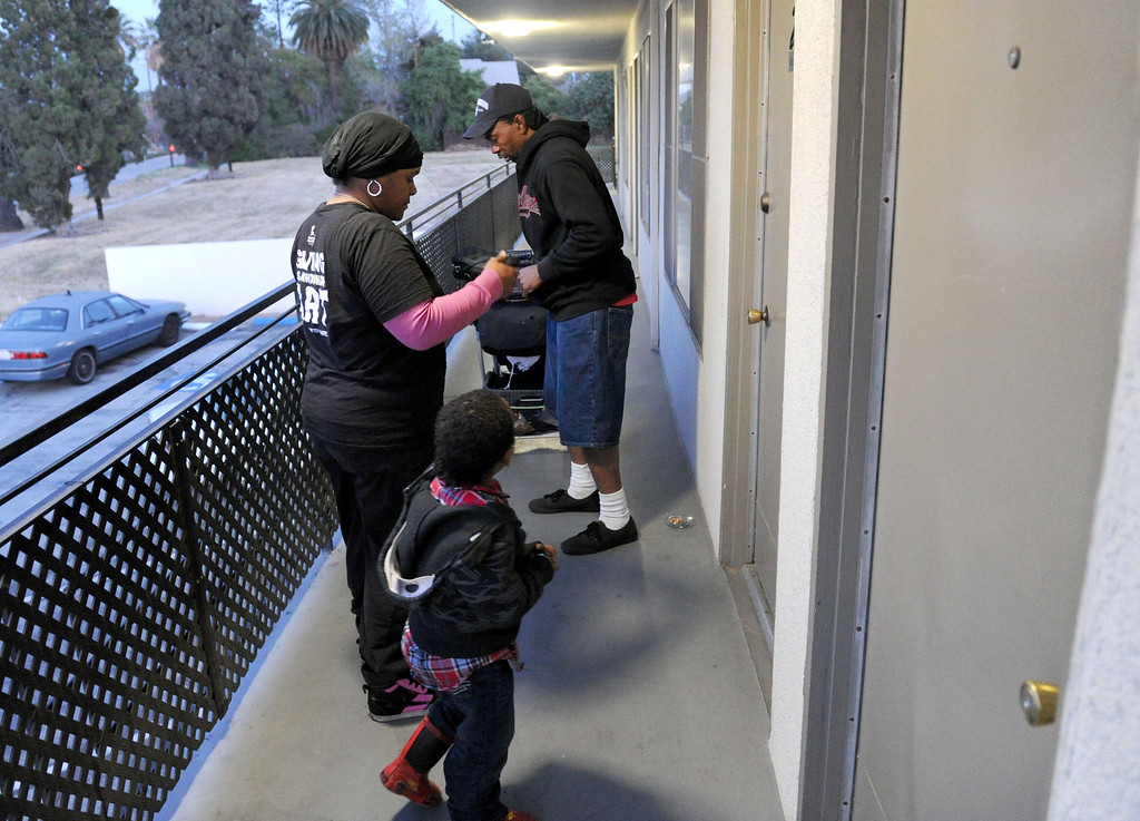 . (John Valenzuela/Staff Photographer)  Danielle Parks, Curtis Wagner and son Curtis Jr.of Redlands, get back to their motel room where they\'ve been living for the past three week.  After getting evicted from their home in San Bernardino in December, Parks and Wagner have had to struggle to make ends meet, getting help from family and handouts from the community, along with panhandling to earn money for their motel room.
