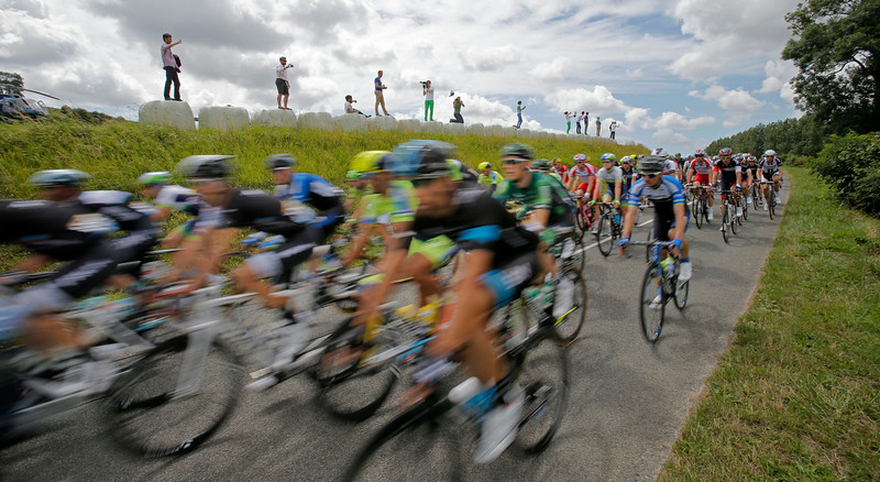 . Spectators take pictures of the pack as it passes during the fourth stage of the Tour de France cycling race over 163.5 kilometers (101.6 miles) with start in Le Touquet and finish in Lille, France, Tuesday, July 8, 2014. (AP Photo/Christophe Ena)