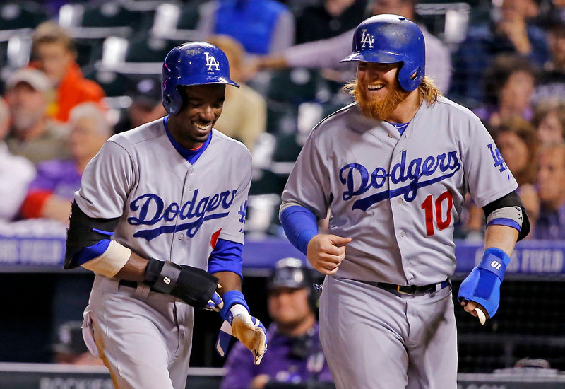 . Los Angeles Dodgers\' Dee Gordon (9) and Justin Turner (10) smile after scoring against the Colorado Rockies during the sixth inning of a baseball game Monday, Sept. 15, 2014, in Denver. (AP Photo/Jack Dempsey)