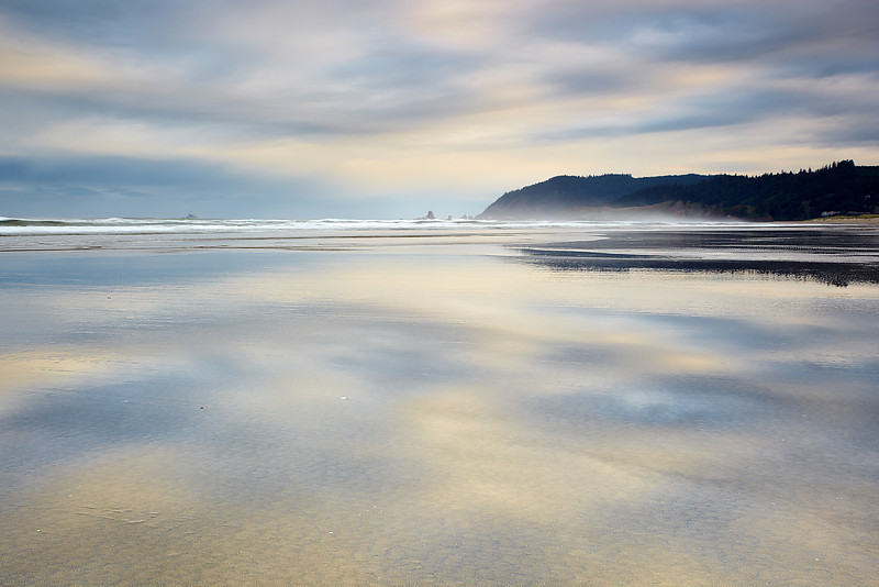 This is the view looking north from Cannon Beach towards Ecola State Park in Oregon.  Low tied is the best time to capture a scene like this.  In the full sized version, you can easily see the little Tillamook Lighthouse.