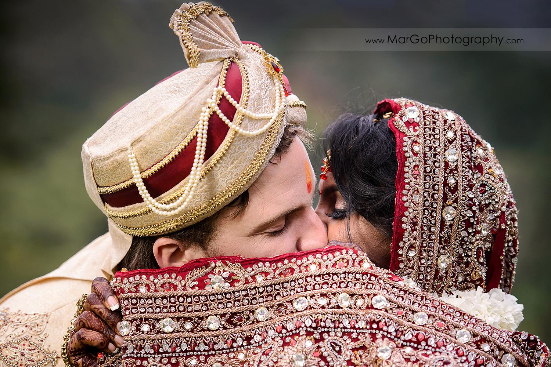 bride and groom kissing during indian wedding ceremony at Brazilian Room - Tilden Regional Park, Berkeley