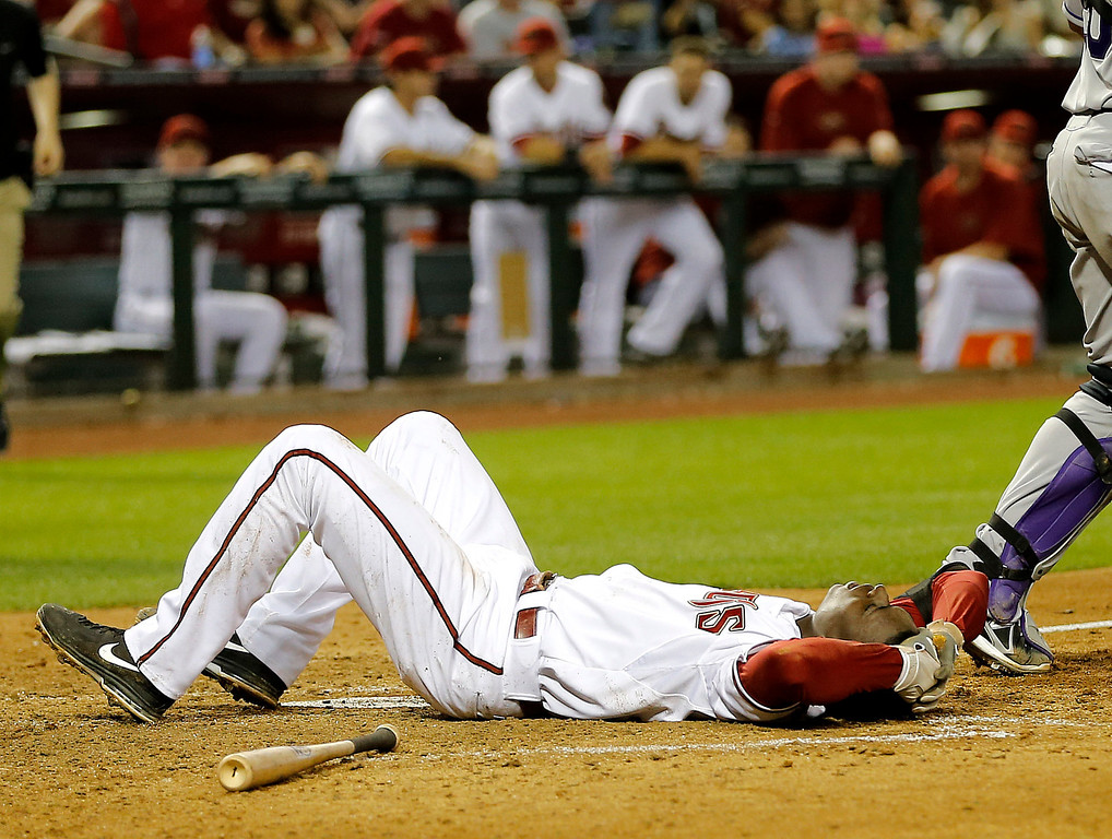 . Arizona Diamondbacks\' Didi Gregorius lies on the ground after being hit in the head by Colorado Rockies pitcher Josh Outman during the seventh inning of a baseball game, Friday, April 26, 2013, in Phoenix. (AP Photo/Matt York)