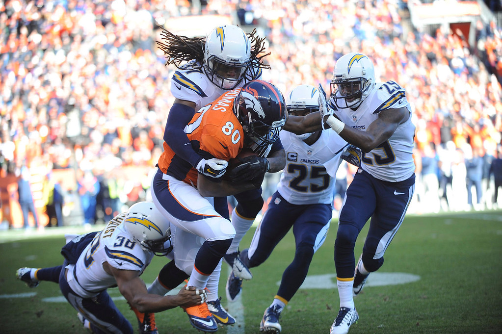 . Denver Broncos tight end Julius Thomas is tackled by Jahleel Addae after catching a pass in the first quarter at Sports Authority Field at Mile High. (Photo by Steve Nehf/The Denver Post)
