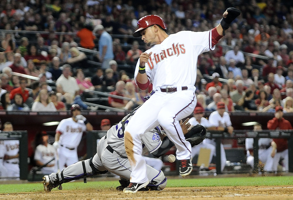 . PHOENIX, AZ - APRIL 26:  Gerardo Parra #8 of the Arizona Diamondbacks scores as catcher Wilin Rosario #20 of the Colorado Rockies drops the ball in the third inning at Chase Field on April 26, 2013 in Phoenix, Arizona.  (Photo by Jennifer Stewart/Getty Images)