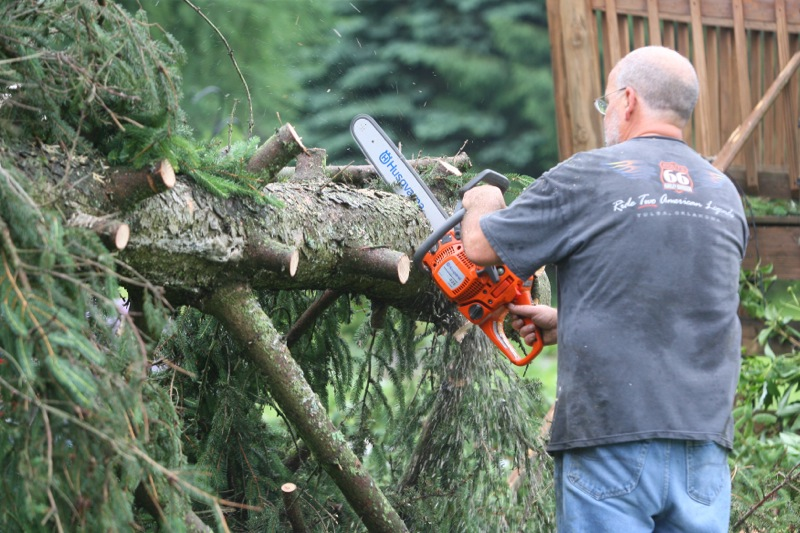 . Jeff Hawthorne uses a chainsaw to clear a fallen tree at his mothers home at the intersection of West Main Street and Station Street in Verona following an early morning storm on Wednesday, June 18, 2014. JOHN HAEGER @ONEIDAPHOTO ON TWITTER/ONEIDA DAILY DISPATCH