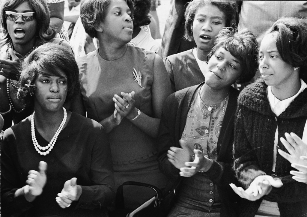 . To pass the long morning, young women clap and sing along to a freedom song between speeches at the March on Washington for Jobs and Freedom, Washington DC, August 28, 1963. (Photo by Express Newspapers/L360/Getty Images)
