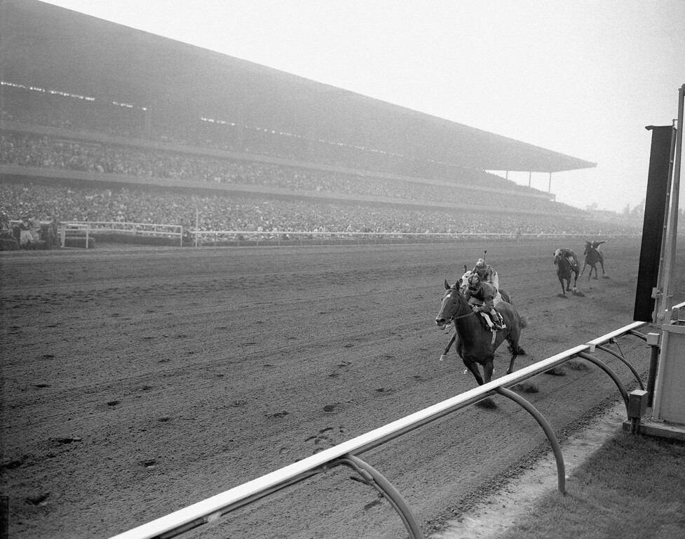 . Thundering to a new world record for the mile in 1:33 1/5 at Hollywood Park in Inglewood, California  June 9, 1956, Swaps (2, on rail) with Willie Shoemaker up, crosser the finish line to win the $50,000 added Argonaut handicap. Bobby Brocato, ridden by Johnny Longden, pressed him all the way and came in second (outside). Porterhouse, several lengths back was third. Swaps bettered the record held by Citation of 1:33 3/5 set in 1950 at Golden Gate Fields. (AP Photo/Harold P. Matosina)