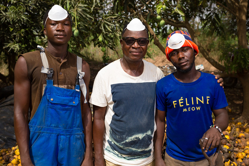 Three workers at one of the Utilization of Organic Waste to Improve Agricultural Productivity (UOWIAP) farms pose in front of a pile of fruit. The UOWIAP is led by University of Ghana and aims to enhance food security.