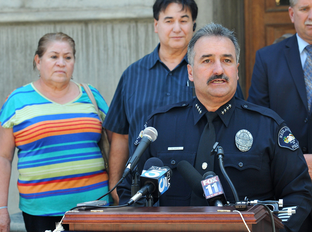 . (John Valenzuela/Staff Photographer) Redlands Police Chief Mark Garcia gives an update in the murder investigation of Sylvia Flores, as her parents Sylvia and Robert Flores listen, during a press conference outside the police annex in Redlands, CA.Tuesday, September 12, 2013. Flores, a 23-year-old woman from Perris, CA. who\'s body was found in a orange groves near Citrus Plaza shopping center in Redlands.