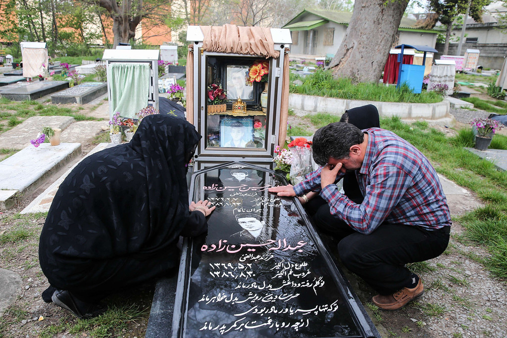 . Samereh Alinejad (L) and Abdolghani Hosseinzadeh (R) mourn at the grave of their son Abdolah Hosseinzadeh who was killed by a fellow Iranian, Balal, in a street fight with a knife in 2007, after they spared the life of their son\'s convicted murderer during his execution ceremony in the northern city of Nowshahr on April 15, 2014.  AFP PHOTO/ARASH KHAMOOSHI/AFP/Getty Images