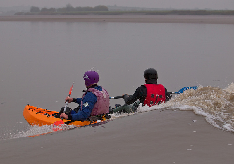 Canoeists enjoying the bore as they ride the leading wave.