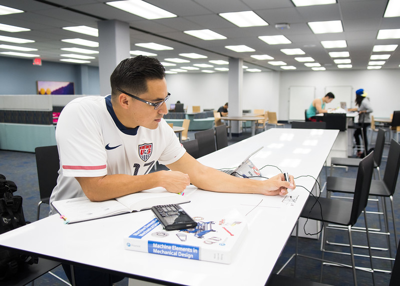Carlos Gaytan works on a whiteboard table in the Mary and Jeff Bell Library.