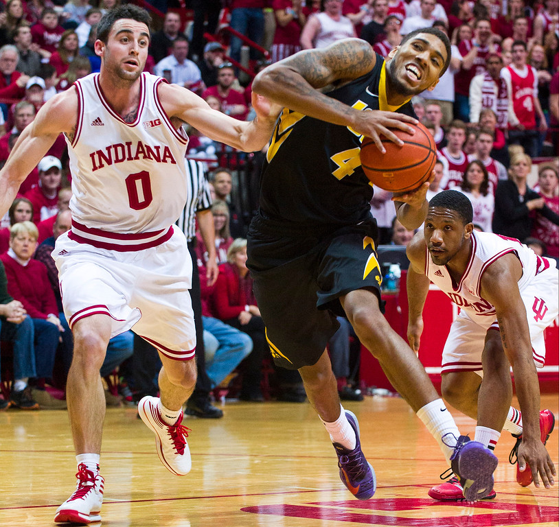 . Iowa\'s Roy Devyn Marble (4) reacts as he is fouled by Indiana\'s Will Sheehey (0) in the first half of an NCAA college basketball game on Thursday, Feb. 27, 2014, in Bloomington, Ind. (AP Photo/Doug McSchooler)