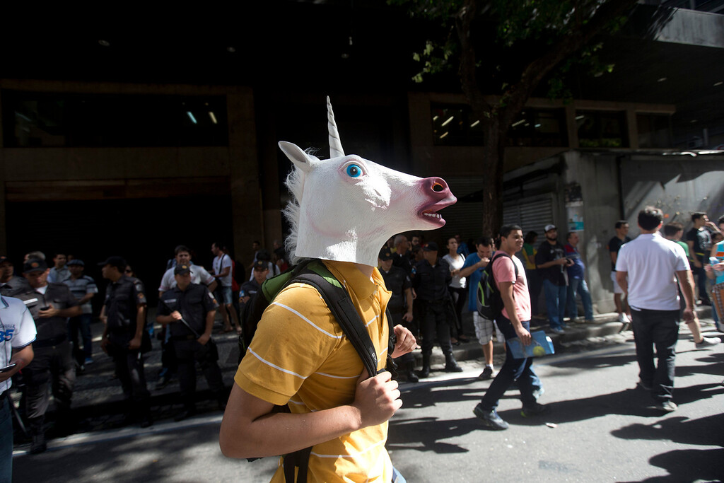 . An anti-World Cup demonstrator, wearing a unicorn mask, attends a protest demanding better public services and protesting the money spent on the World Cup soccer tournament, in downtown Rio de Janeiro, Brazil, Thursday, June 12, 2014, just hours before the first World Cup match was to be played in Sao Paulo. (AP Photo/Silvia Izquierdo)