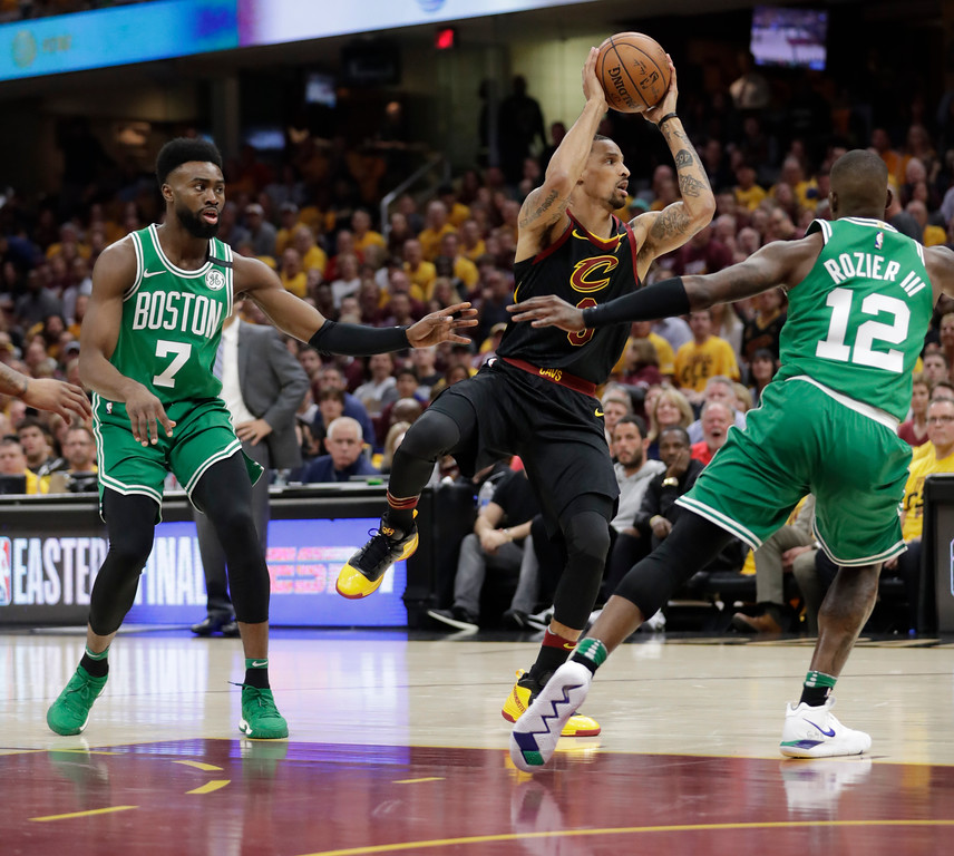 . Cleveland Cavaliers\' George Hill (3) looks to pass between Boston Celtics\' Terry Rozier (12) and Jaylen Brown (7) in the first half of Game 3 of the NBA basketball Eastern Conference finals, Saturday, May 19, 2018, in Cleveland. (AP Photo/Tony Dejak)