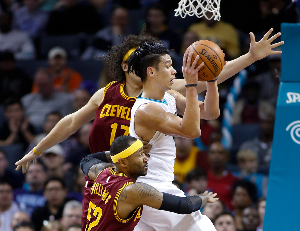 . Charlotte Hornets guard Jeremy Lin, center, passes out of a double-team by Cleveland Cavaliers center Anderson Varejao, back, and guard Mo Williams during the second half of an NBA basketball game Wednesday, Feb. 3, 2016 in Charlotte, N.C. Charlotte won 106-97. (AP Photo/Nell Redmond)