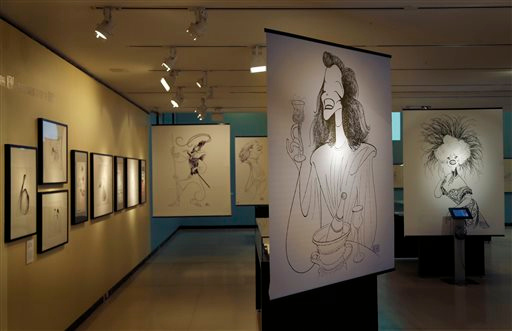 Description of . Drawings by Al Hirschfeld are displayed in an exhibit on the artist at the Library for the Performing Arts in New York, Wednesday, Oct. 16, 2013. The exhibit, which opens Thursday, Oct. 17, 2013, showcases work through Hirschfeld's career. (AP Photo/Seth Wenig)